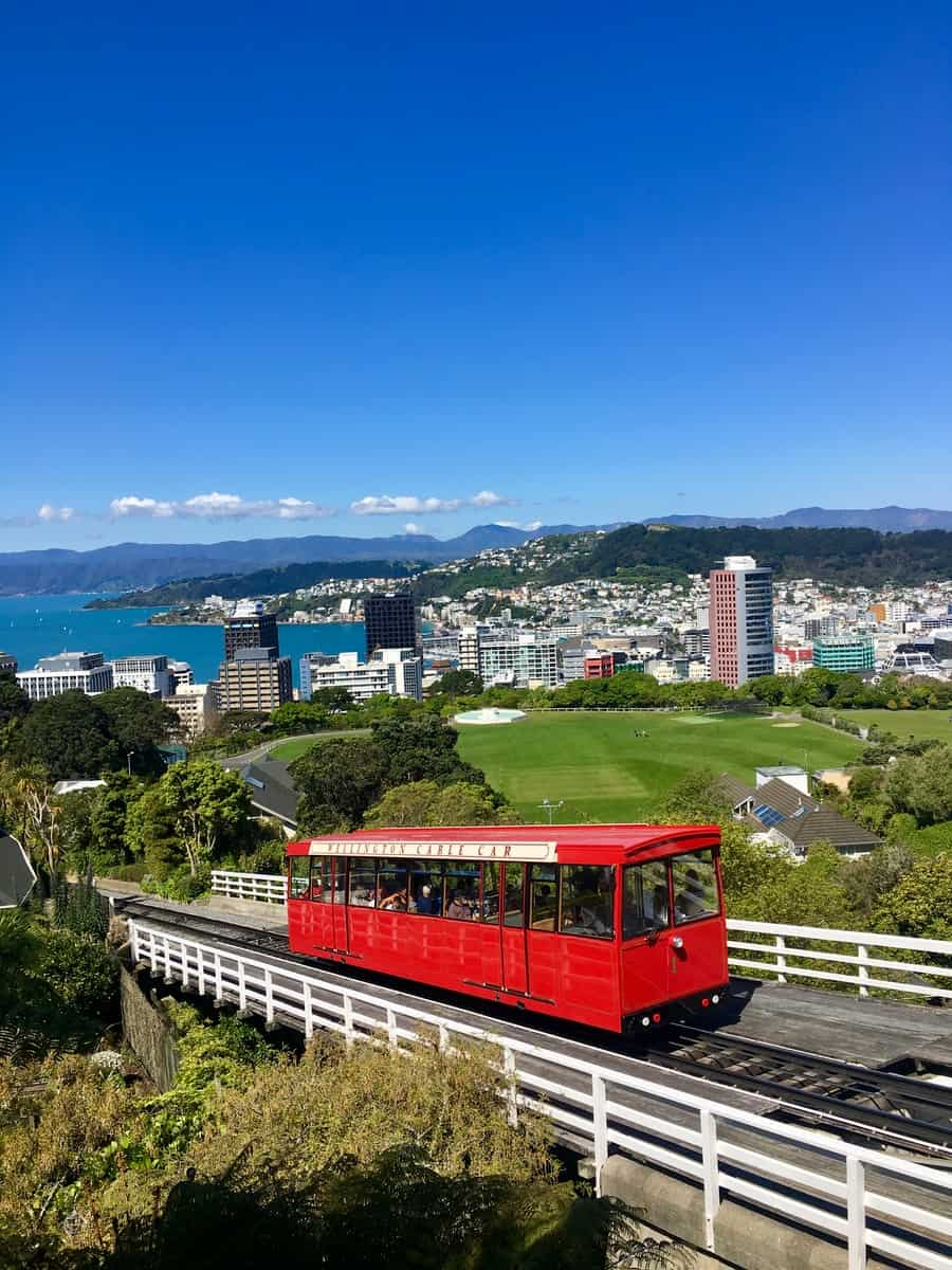 red train on rail with cityscape view underlue sky